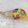 Букет из 9 радужных роз в крафте фото