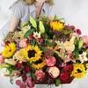 Композиция из подсолнухов, роз, альстромерий и лилий в плетёной корзине фото